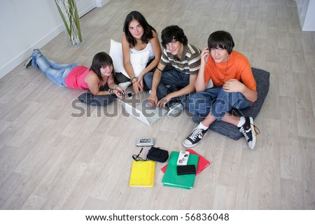 Group of teenagers listening to music near a boy sitting in front of a laptop computer - stock photo