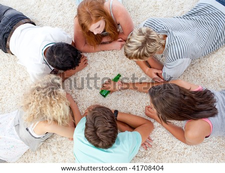Group of teenagers lying on the floor and playing with a bottle - stock photo