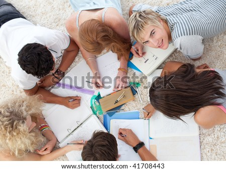 Group of Teenagers lying on the ground studying together - stock photo