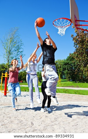 Group of teenagers playing street basketball - stock photo