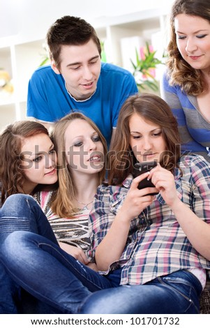 Group of teenagers reading interesting sms on smart phone - stock photo