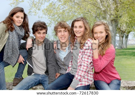 Group of teenagers sitting outside - stock photo