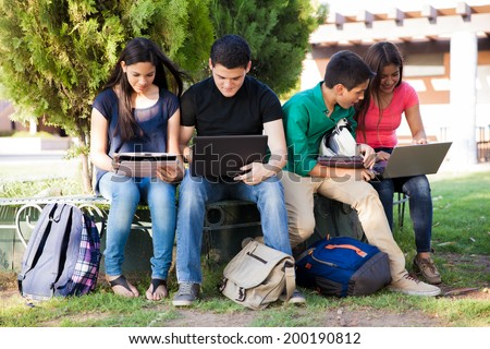 Group of teenagers social networking using several tech devices in high school - stock photo
