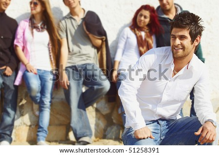 group of teenagers standing against the wall with their leader in white shirt and jeans sitting infront - stock photo