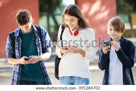 Group of teenagers with mobile phones on the street. Focus on girl - stock photo
