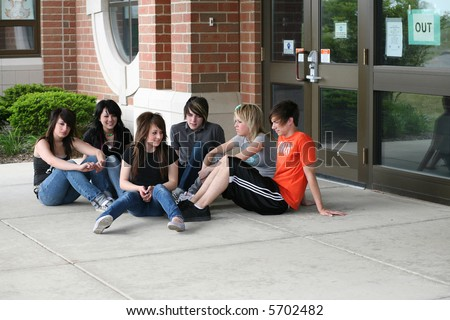 group of teens sitting outside front entrance of school - stock photo