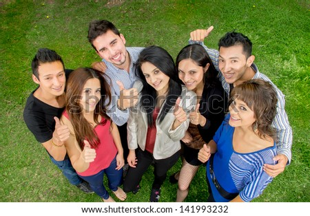 Group of teens thumbing up outdoors - stock photo