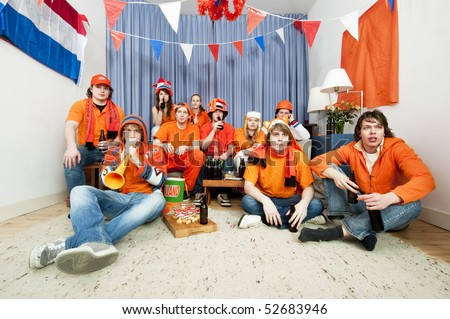 Group of ten sports fans watching their national team on television at home - stock photo