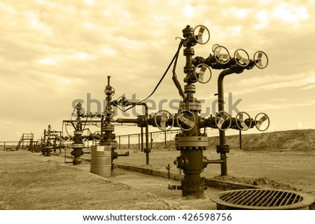 Group of the industrial wellheads and pipeline with valves. Oil and gas theme. Toned sepia. - stock photo