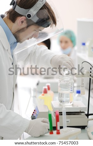 Group of the students working at the laboratory with liquids in tubes and electronics - stock photo