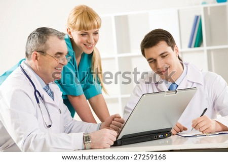 Group of therapists looking at laptop screen and discussing new method of treatment - stock photo