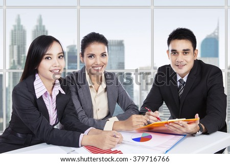 Group of three Asian businesspeople sitting in the office while discussing together on the meeting and smiling at the camera - stock photo