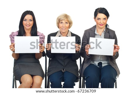 Group of three business women sitting on chairs in a line showing blank pages isolated on white background - stock photo