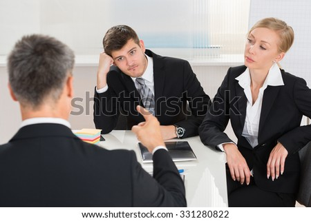 Group Of Three Businesspeople Having Argument At Workplace - stock photo