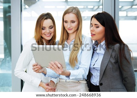 Group of three businesswomen looking at a digital tablet held by one of them - stock photo