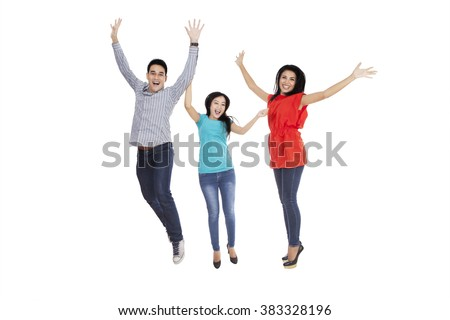 Group of three cheerful people jumping together in the studio, isolated on white background - stock photo