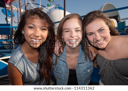 Group of three cheerful teenage girls embracing each other - stock photo