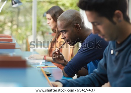 group of three college students studying in library, one of them eating a snack. Horizontal shape, side view, waist up, copy space - stock photo