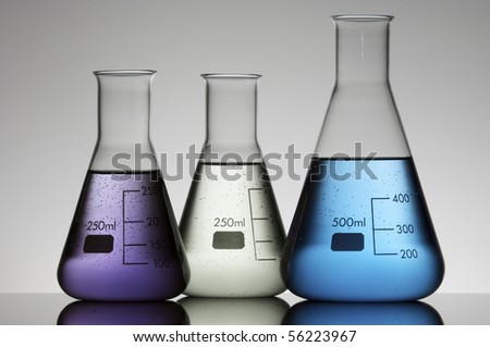 group of three conical flasks containing liquid shiny - stock photo