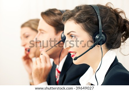Group of three customer care representatives in a call center with headphones - stock photo