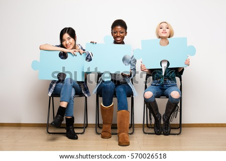 group of three different ethnic woman waiting in chairs with puzzle pieces