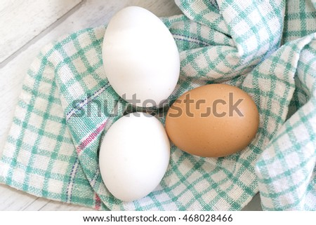 Group of three eggs on colored cloth and wooden table