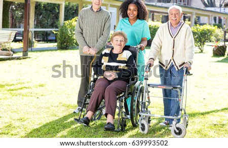 Group of three elderly people standing in the garden smiling with african nurse.
