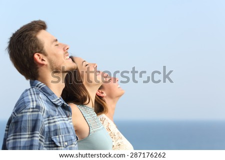 Group of three friends breathing deep fresh air on the beach - stock photo