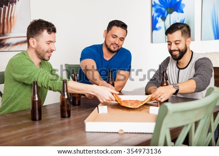 Group of three friends eating pizza and drinking some beer at home