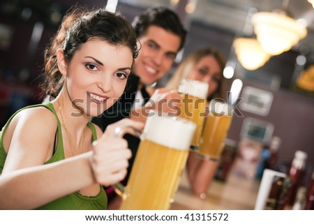 Group of three friends in a bar drinking beer - selective focus on beautiful woman in front, whole group pointing their glasses towards viewer