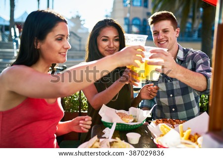 group of three friends making a toast with beer cups at lunch on summer day