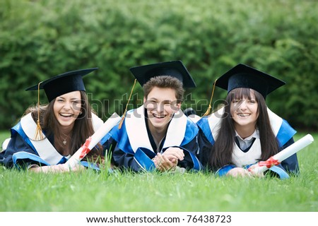 group of three graduation students lying in the park cheerful and happy - stock photo