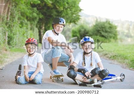 Group of three happy smiling children different ages, posing with rolling skates, helmets and protection at the park, summertime - stock photo