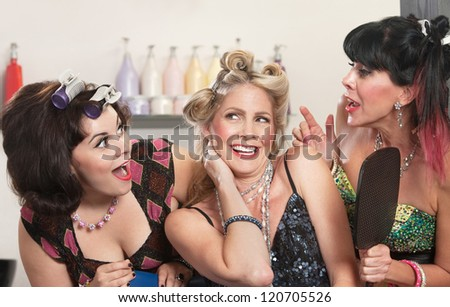 Group of three happy women talking in hair salon