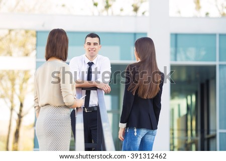Group of three happy young business people on a coffee break in front of the office building. Portrait of young man looking at camera and rear view of two women looking at him. - stock photo