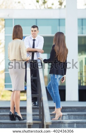 Group of three happy young business people on a coffee break in front of the office building. Front view of young man talking to his coworkers and rear view of two women looking at him. - stock photo