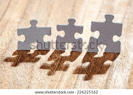 Group of three jigsaw puzzle pieces on a table lit by back light. Shallow depth of field - stock photo