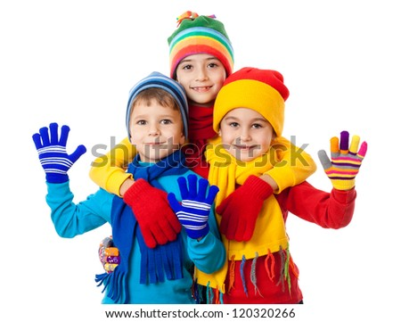 Group of three kids in bright winter clothes, isolated on white - stock photo