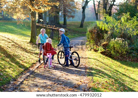 Group of three kids riding their bikes in the park. Children enjoying sunny warm autumn day outdoors. Brothers and sister having fun in the fall.