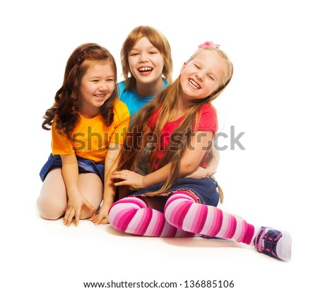 Group of three kids, two girls and boy together, diversity looking happy, laughing, hugging, sitting isolated on white - stock photo