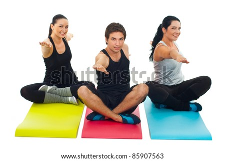 Group of three people doing yoga and sitting on colorful mats - stock photo