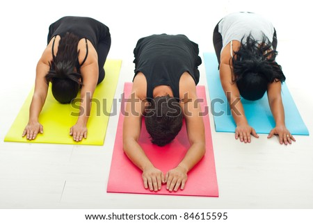 Group of three people doing yoga exercise on colorful gymnastics mats - stock photo