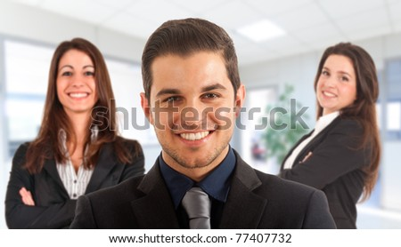 Group of three smiling businesspeople in an office environment. - stock photo