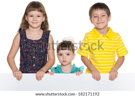 Group of three smiling children hold a white sheet of paper - stock photo