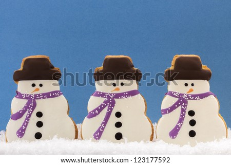 Group of three snowmen cookies with purple scarves and chocolate hats in snow on blue background - stock photo