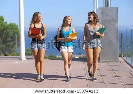 Group of three student teenagers walking towards camera with the sky in the background - stock photo