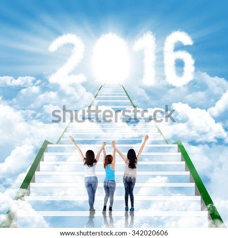 Group of three teenage girls standing on the staircase with clouds shaped numbers 2016 and future door