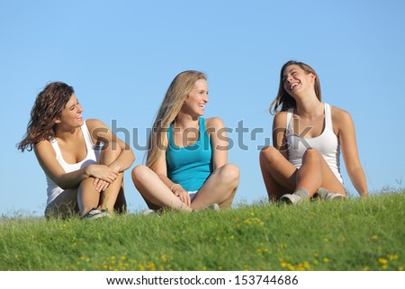 Group of three teenager girls laughing and talking on the grass with the sky in the background - stock photo