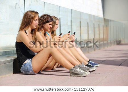 Group of three teenager girls sitting on the floor typing on the mobile phone - stock photo