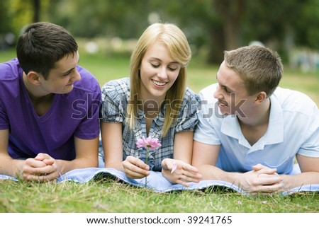 Group of Three Teens Lying on Blanket in a Park - stock photo